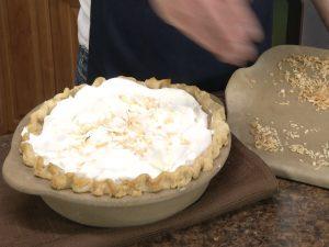 Kristy sprinkles coconut on pie.