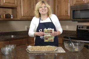 Kristy poses with the Unforgettable cookbook and completed homemade granola.