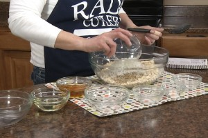 Kristy adds coconut to oats mixture in preparation of granola.