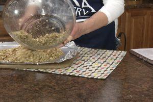 Kristy places granola onto baking foil.