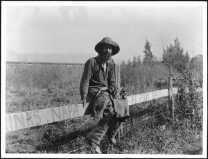 A hobo poses for a photograph while sitting on a fence.