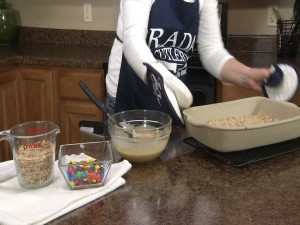 Kristy removes pan from oven.