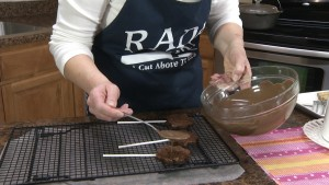 Kristy coats brownie sticks in chocolate.