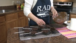 Kristy covers other side of brownie sticks with chocolate.
