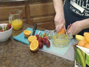 Kristy squeezes an orange to make orange juice.