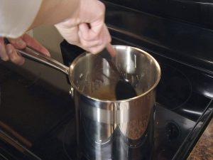 Kristy stirs caramel in saucepan.