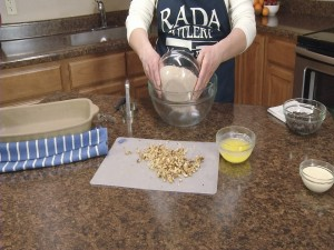 Kristy adds cake mix to bowl.