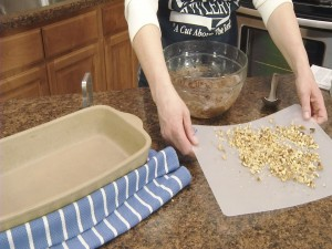 Kristy prepares to place nuts in mixture.