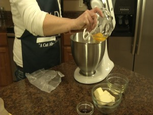 Kristy adds eggs to mixer.