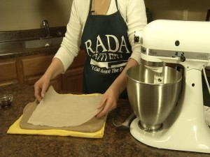 Kristy places parchment paper on Rada stoneware cookie sheet.