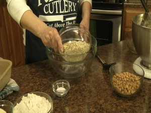 Kristy adds oats to mixing bowl.