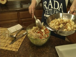 Kristy adds toasted ramen to salad.