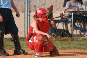 A softball catcher on the field.