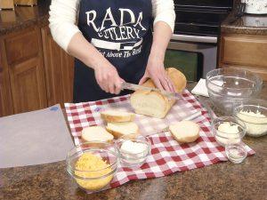 Kristy slices fresh Italian bread.