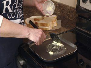 Kristy melts butter on skillet.