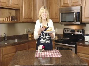 Kristy poses with completed Ultimate Grilled Cheese and 101 Recipes with Cream Cheese cookbook.