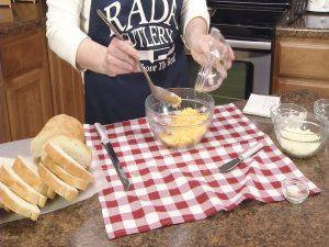 Kristy adds shredded cheddar cheese.