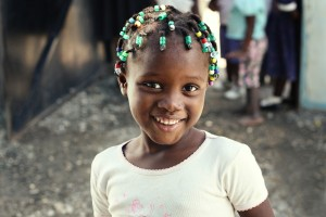 An adorable Haitian child smiles for the camera.