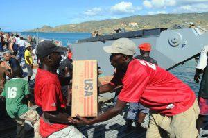 Two Haitian men unload US aid supplies.