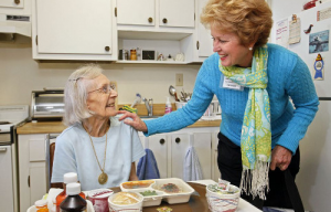 A Meals on Wheels volunteer speaks with a recipient.