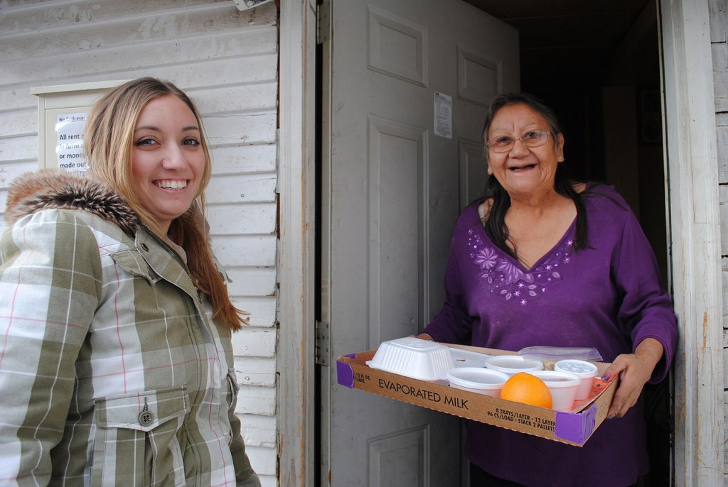A volunteer delivers a meal to a senior citizen. Fundraising for senior meal programs such as Meals on Wheels is best done with Rada Cutlery.
