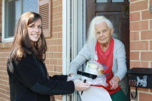 A volunteer delivers a senior a nutritious meal.