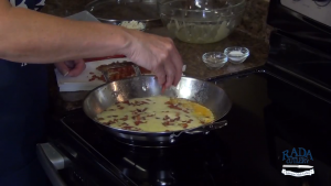 Kristi adds bacon to eggs.