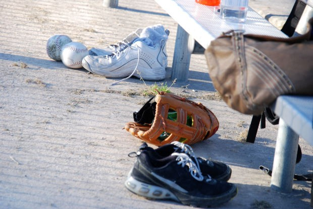 Softball equipment sits near the bench