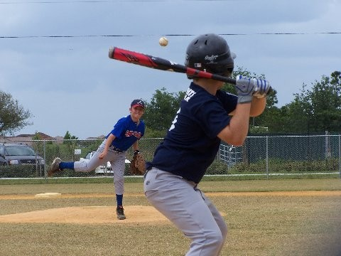 A youth baseball pitcher pitches the ball.