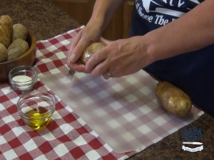 Kristi covers potatoes in olive oil.