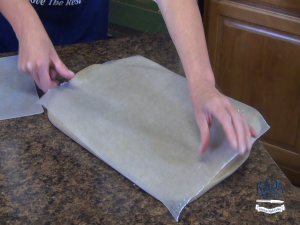 Kristi coats the Rada Cookie Sheet with wax paper.