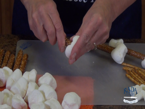 Kristi inserts the pretzel rods into large marshmallows.