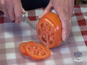 Kristi slices tomato.