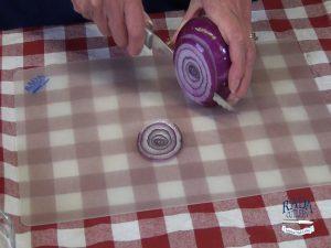 Kristi cuts a red onion.
