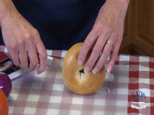 Kristi cuts a bagel in half.