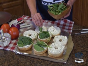Kristi places spinach on bagels.