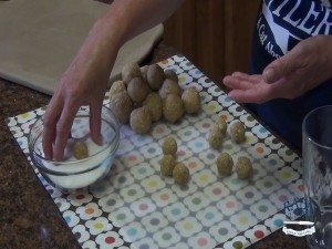 Kristi dips cookie dough balls in sugar.
