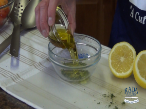 Kristi adds olive oil to fresh basil.