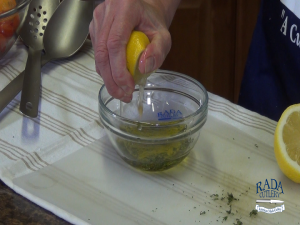 Kristi squeezes lemon juice into olive oil and basil.