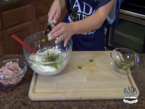 Jess places dill pickles in a mixing bowl.