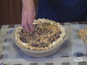 Kristi places peanuts on top of pie.