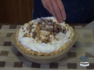 Kristi places Snickers candy pieces on top of a pie.