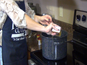 Jess adds spices to chicken stock.