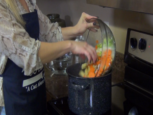 Jess adds her vegetables to chicken stock.