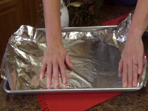 Kristi spreads tin foil on baking sheet.