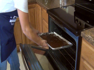 Kristi places her brownie mix in the oven.