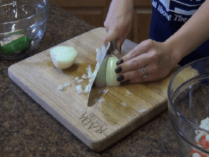 Jess chops an onion with a Rada French Chef knife.