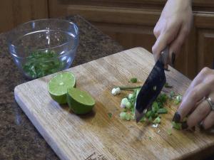 Jess chops green onions.