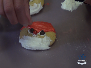 Kristi adds eyes and nose to Santa Cookies.