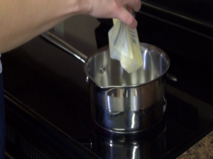 Jess adds butter to a saucepan.